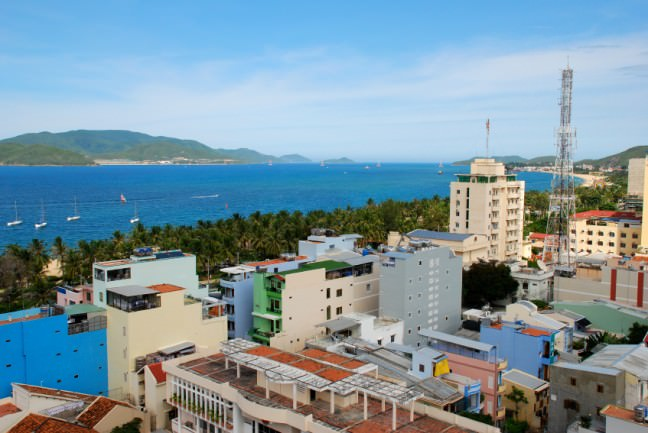 The panoramic scenery of Nha Trang, a beautiful sea-side town to consider visiting when living in Vietnam. The buildings look modern, boxy, almost like toys. The colors look art deco.